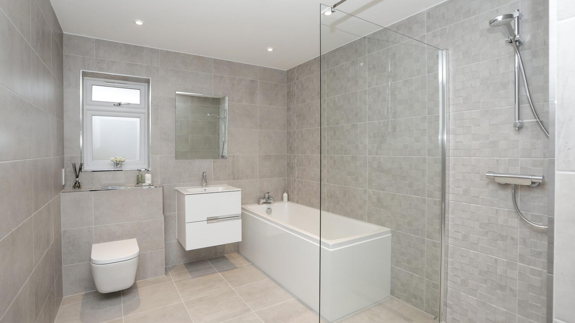 Bathroom with grey tiling, sink, toilet and bath