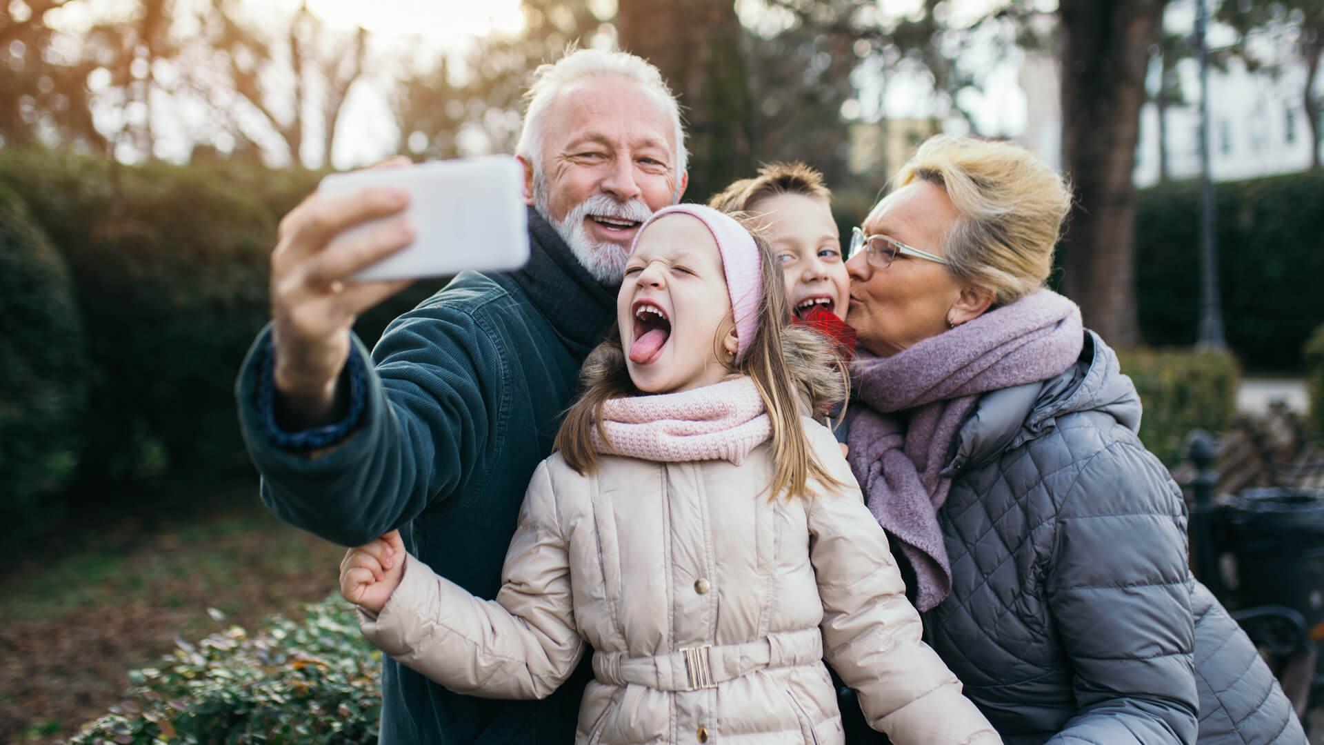 Retired grandparents taking a selfie with grandchildren