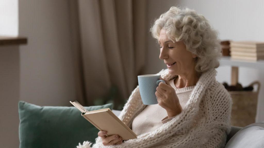 Elderly woman reading and drinking tea