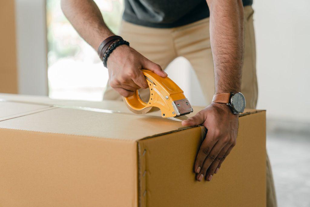 Man cutting open cardboard box